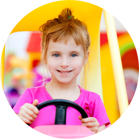 a girl driving a play car