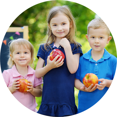 three children holding an apple